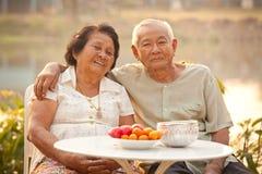 Pares mayores felices que se sientan al aire libre Imagenes de archivo
