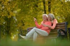 Pares mayores felices que se sientan en banco foto de archivo libre de regalías
