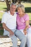 Pares mayores felices que se sientan en banco en sol Imagenes de archivo