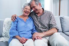 Pares mayores felices que se sientan en el sofá y el abarcamiento Imagen de archivo
