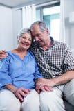 Pares mayores felices que se sientan en el sofá y el abarcamiento Imagen de archivo libre de regalías