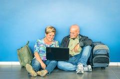 Pares mayores felices que se sientan en piso con el ordenador portátil en el aeropuerto Imagenes de archivo