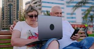 Pares mayores felices que se sientan en un banco en el verano en una ciudad moderna con un ordenador port?til en el fondo de rasc almacen de video