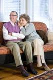 Pares mayores felices que se sientan junto en el sofá Fotos de archivo