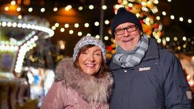 Pares mayores felices que sonríen en el mercado de la Navidad almacen de metraje de vídeo