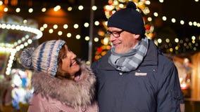 Pares mayores felices que sonríen en el mercado de la Navidad metrajes