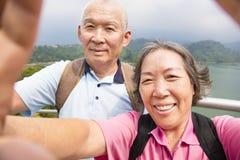 Pares mayores felices que toman la imagen con el selfie elegante del teléfono Foto de archivo