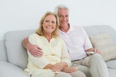 Pares mayores felices relajados con teledirigido en casa Fotografía de archivo