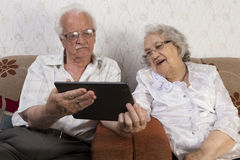 Pares mayores felices usando la computadora de la tableta Fotografía de archivo libre de regalías