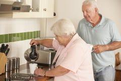 Pares mayores jubilados en la cocina que hace la bebida caliente junto Imágenes de archivo libres de regalías