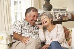 Pares mayores jubilados que se sientan en el hogar de Sofa Talking On Phone At junto Foto de archivo libre de regalías