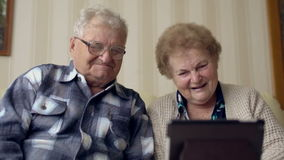Pares mayores maduros que disfrutan de tecnología moderna usando la PC de la tableta Personas mayores que comunican con Internet  metrajes