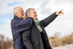 Pares mayores mayores felices que caminan en la playa Imagen de archivo libre de regalías