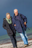Pares mayores mayores felices que caminan en la playa Fotos de archivo