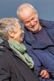 Pares mayores mayores felices que caminan en la playa Imagenes de archivo