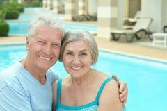 Pares mayores por la piscina Fotos de archivo libres de regalías