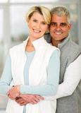 Pares mayores que abrazan a casa Foto de archivo libre de regalías