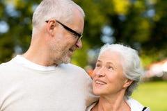 Pares mayores que abrazan en parque de la ciudad Foto de archivo libre de regalías