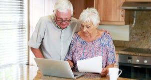 Pares mayores que calculan sus cuentas en el ordenador portátil en la cocina metrajes
