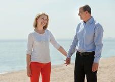 Pares mayores que caminan a lo largo de la playa Imagen de archivo