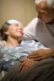 Pares mayores que celebran las manos en la sala de la clínica Imagen de archivo
