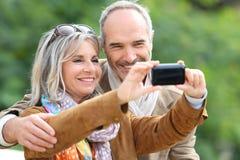 Pares mayores que clavan el recuerdo de la foto con tachuelas con smartphone Foto de archivo