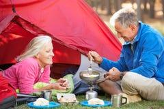 Pares mayores que cocinan el desayuno en acampada imágenes de archivo libres de regalías