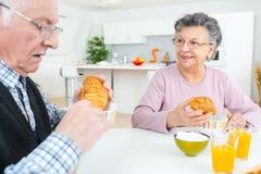Pares mayores que comen el desayuno continental imagen de archivo