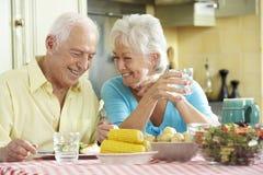 Pares mayores que comen la comida junto en cocina foto de archivo libre de regalías