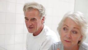 Pares mayores que comprueban la piel en espejo del cuarto de baño almacen de video