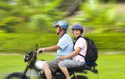 Pares mayores que conducen la motocicleta con el fondo dinámico Foto de archivo libre de regalías