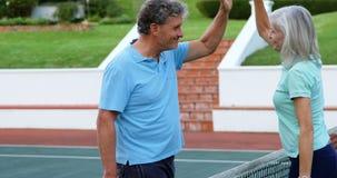 Pares mayores que dan el alto cinco en el campo de tenis 4k almacen de video