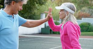 Pares mayores que dan el alto cinco en el campo de tenis 4k almacen de metraje de vídeo