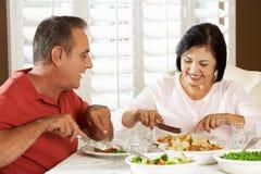 Pares mayores que disfrutan de la comida en casa Imágenes de archivo libres de regalías