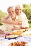 Pares mayores que disfrutan de la comida en jardín Fotografía de archivo
