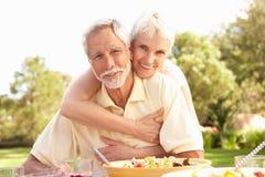 Pares mayores que disfrutan de la comida en jardín Imágenes de archivo libres de regalías