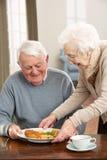 Pares mayores que disfrutan de la comida junto Imagen de archivo