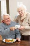 Pares mayores que disfrutan de la comida junto Foto de archivo libre de regalías