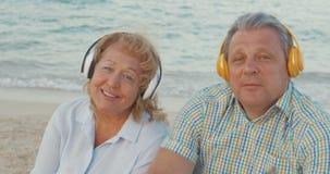 Pares mayores que disfrutan de música en la playa almacen de video