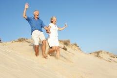 Pares mayores que disfrutan del funcionamiento del día de fiesta de la playa Imagenes de archivo