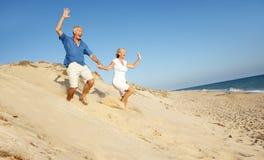 Pares mayores que disfrutan del funcionamiento del día de fiesta de la playa Foto de archivo libre de regalías