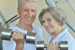 Pares mayores que ejercitan con pesas de gimnasia Imagen de archivo libre de regalías
