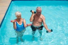 Pares mayores que ejercitan con pesas de gimnasia en la piscina Foto de archivo libre de regalías