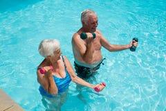 Pares mayores que ejercitan con pesas de gimnasia en la piscina Fotografía de archivo