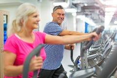 Pares mayores que ejercitan en gimnasia foto de archivo