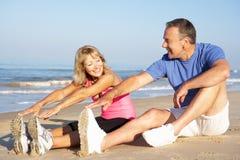 Pares mayores que ejercitan en la playa Foto de archivo