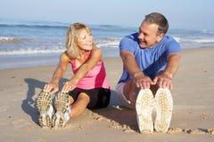 Pares mayores que ejercitan en la playa Fotografía de archivo libre de regalías