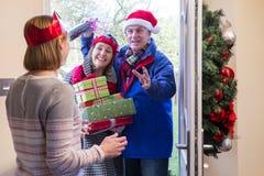 Pares mayores que entregan presentes en la Navidad Fotos de archivo