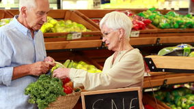 Pares mayores que escogen verduras en supermercado almacen de metraje de vídeo