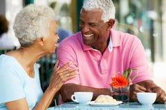 Pares mayores que gozan del bocado en el café al aire libre Imágenes de archivo libres de regalías